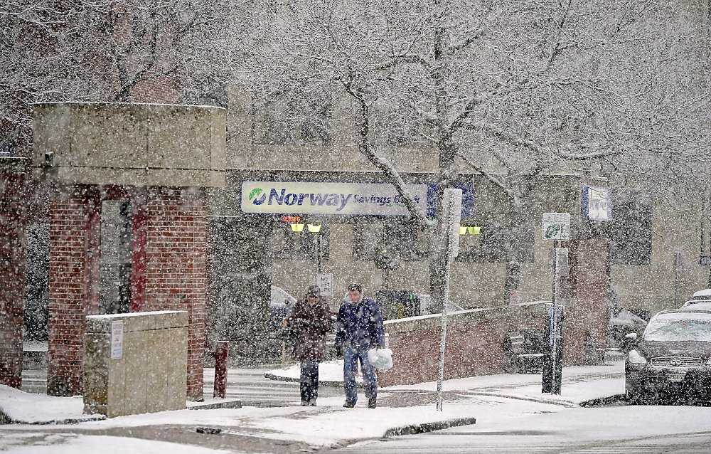 A couple walk up Federal Street on Saturday as the snowfall begins to intensify in Portland.