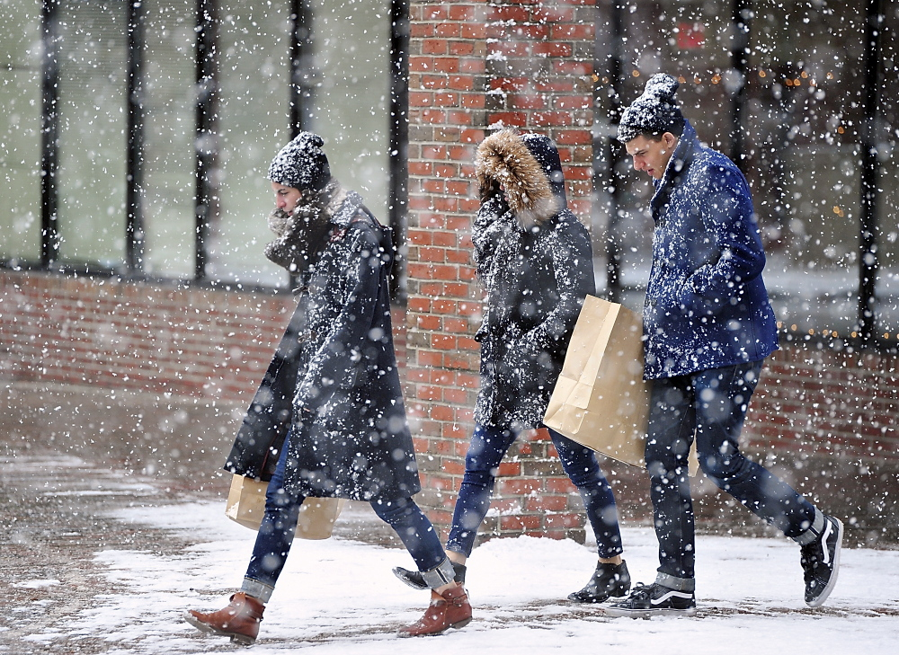 Maxi Roberts of Portland leads her friends Sharon Lieberman and Sean Ellman, both of New York City, home through the falling snow after shopping in the Old Port on Saturday.