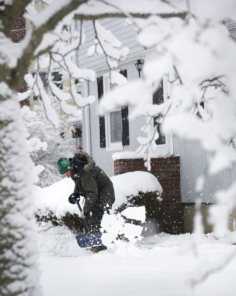 Peter Pizzo of Westbrook shovels in front of his house on Sunday as heavy snow continues to fall and cling to tree branches.
