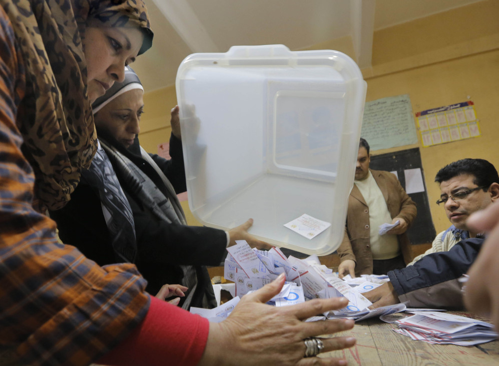 Egyptian election workers empty a ballot box in Cairo on Wednesday, the second and final day of a referendum on a new constitution. Four people were killed in clashes Friday.