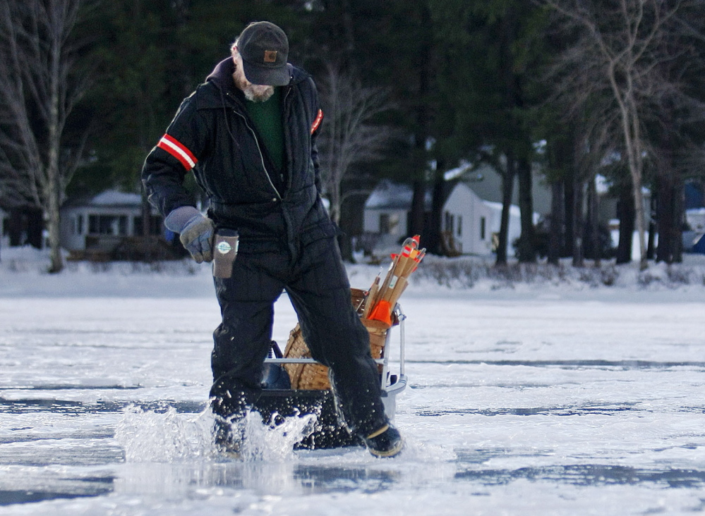 Fred Gallant, Sr., of Saco missteps and splashes into one of many puddles on Long Lake in Naples as he walks out for some ice fishing last week.