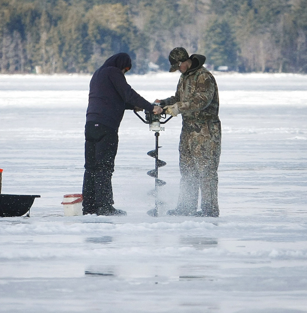 Two fishermen use an ice auger to drill through up to 6 inches of ice on Long Lake, where plenty of trout could be for the taking.