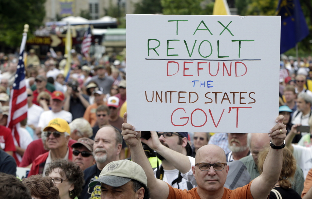 A man holds up a placard during a tea party rally at the U.S. Capitol in Washington in June. As both parties gear up for a midterm election campaign season that will determine the control of Congress, the Republican agenda is at a crossroads.