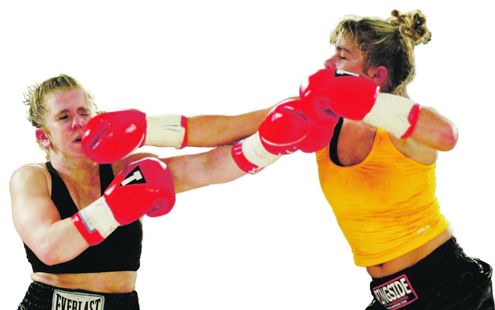 Former Olympic figure skater Tonya Harding, left, takes a right from Emily Gosa during a 2003 bout in Lincoln City, Ore. Harding won the four-round fight by decision.