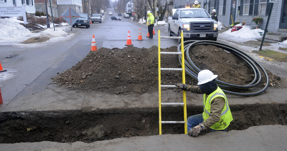 A contractor installs a distribution line across Second Street in Hallowell for Summit Natural Gas of Maine. Work on natural gas lines has created problems for water utilities.