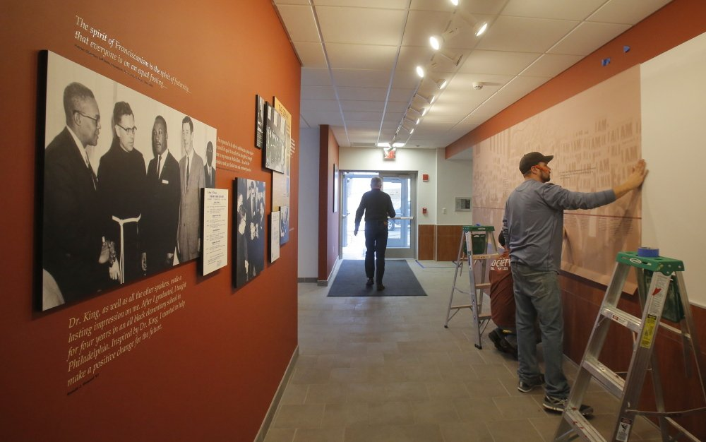 Shawn Theriault smooths out wallpaper with civil rights images on it while installing a Martin Luther King Jr. exhibit in Leonard Hall at the University of New England on Thursday. The civil rights leader came to what was then St. Francis College in May 1964 to speak.