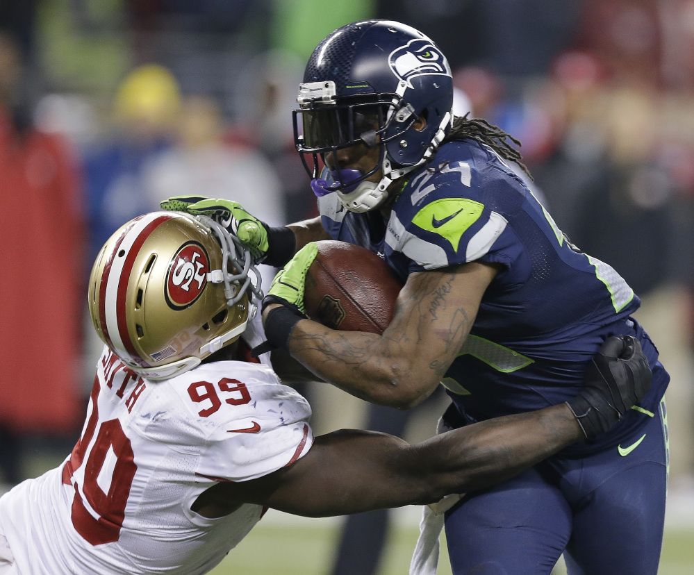 Seattle Seahawks' Marshawn Lynch tries to run past San Francisco 49ers' Aldon Smith during the second half of the NFL football NFC Championship game Sunday, Jan. 19, 2014, in Seattle.