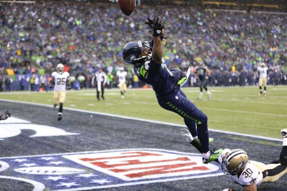Seattle Seahawks wide receiver Percy Harvin, top, jumps for a pass, which he did not catch, over New Orleans Saints defensive back Trevin Wade during the second quarter of an NFC divisional playoff NFL football game in Seattle, Saturday, Jan. 11, 2014. Harvin was injured on the play.