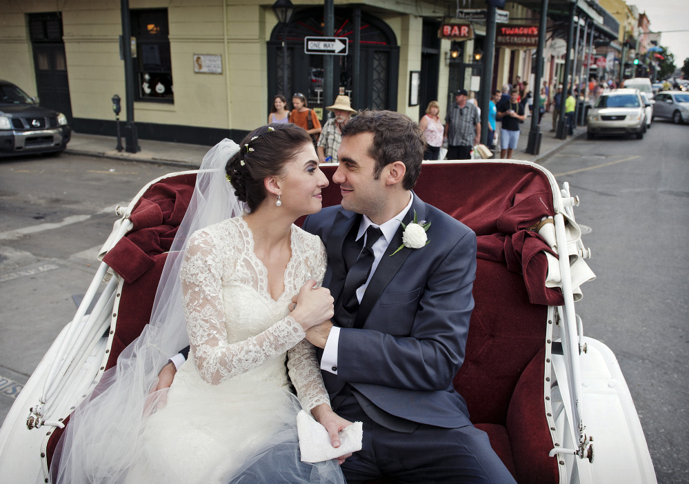 This Oct. 12, 2013 photo provided by Julia Bailey shows Shannon and Justin Peach ride in a carriage after their wedding in New Orleans last October. Shannon's mother, Cheryl Winter, spent $500 for Hartford-based Travelers Insurance to cover her daughter's destination wedding, where her biggest concern was a potential hurricane.