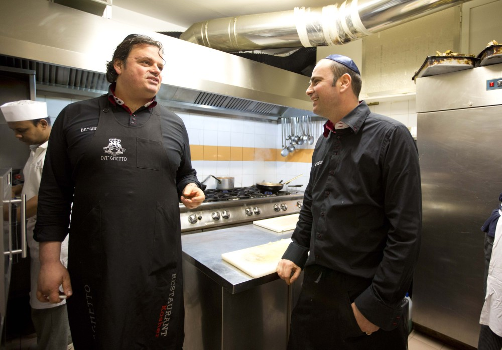Ba'Ghetto restaurant owners Ilan Dabush, left, and his brother Amit talk in the kitchen of their restaurant in Rome on Monday. Their restaurant catered a four-course luncheon hosted by Pope Francis last week for a dozen Argentine rabbis.
