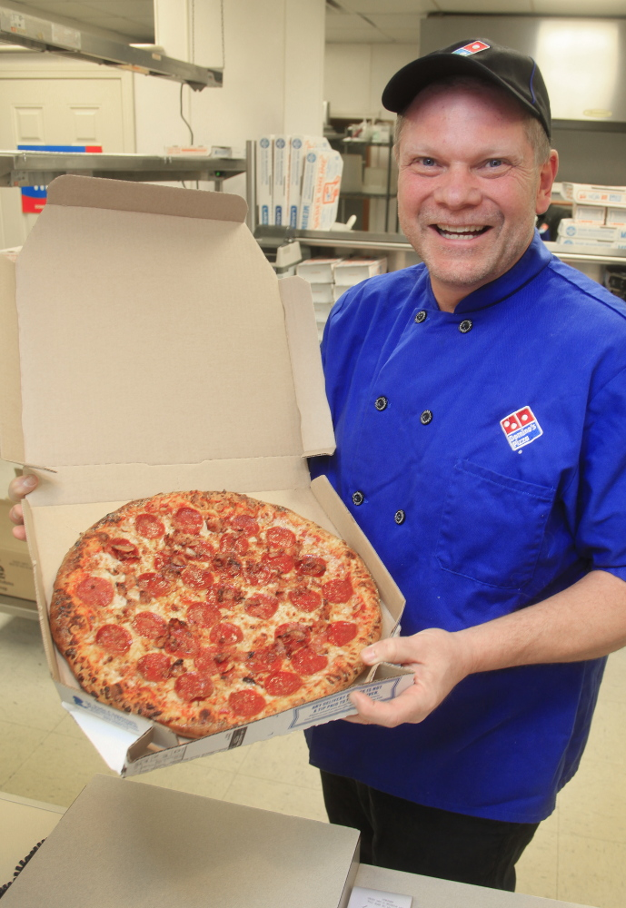 Mike Mullen shows off a fresh pie Monday at his Domino's pizza store in Standish. Mullen is concerned that pending calorie-labeling rules will be complicated and expensive.
