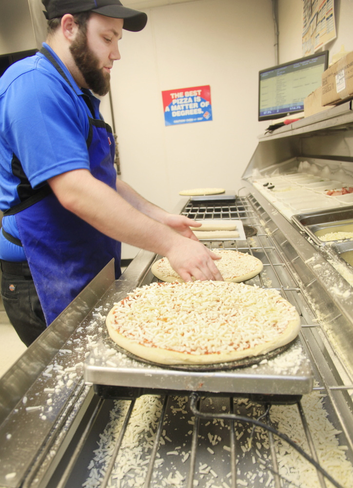 Andrew Legere makes pizzas at Domino's in Standish.