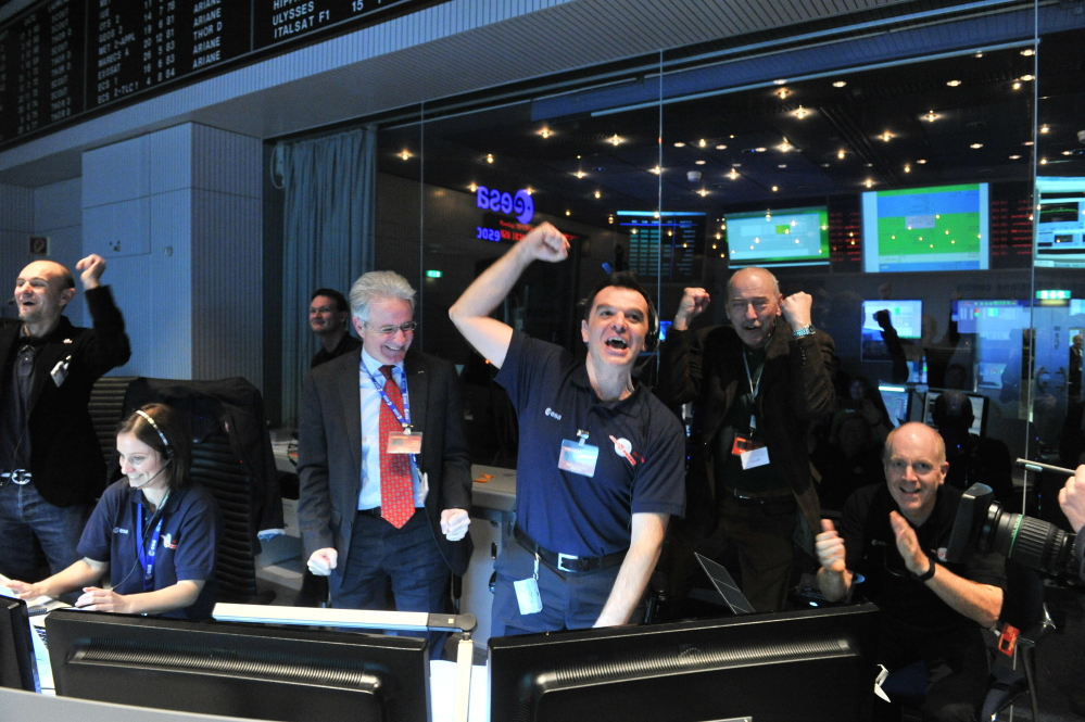 Technicians celebrate after receiving the Rosetta comet-chasing spacecraft's wake-up signal after almost three years of hibernation, in the control room of the European Space Agency in Darmstadt, Germany, on Monday.
