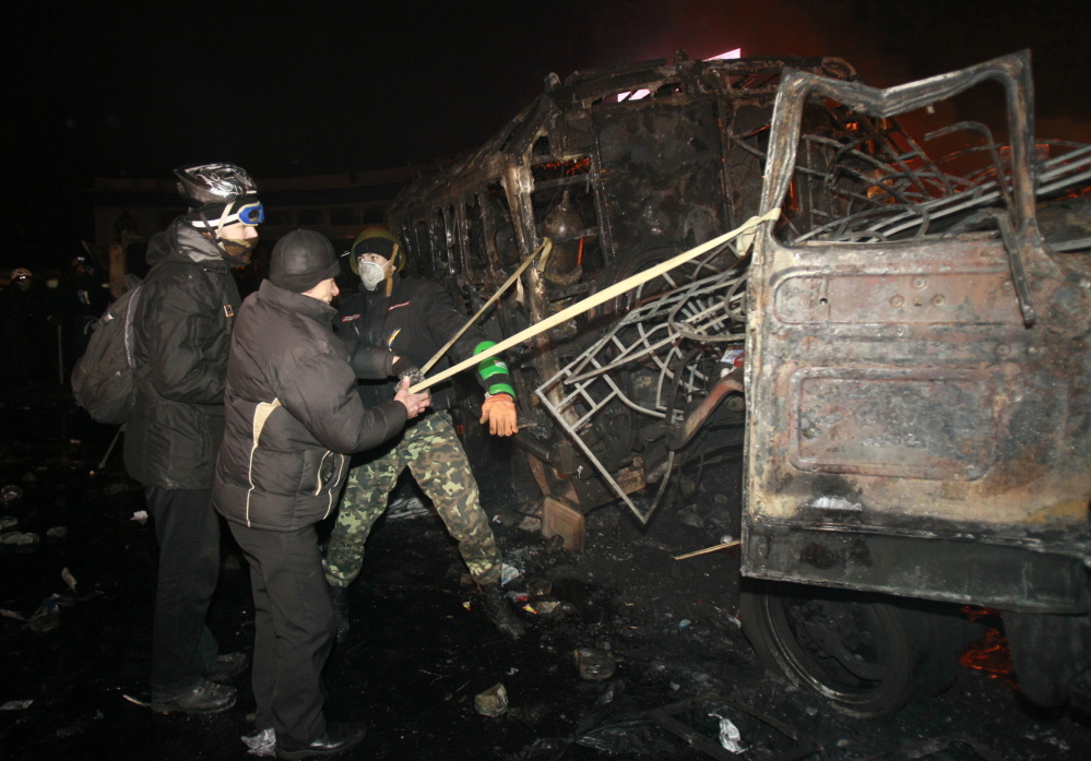Pro-European protesters handle a makeshift catapult that uses the frame of a burned vehicle during clashes with Ukranian riot police in Kiev on Monday.