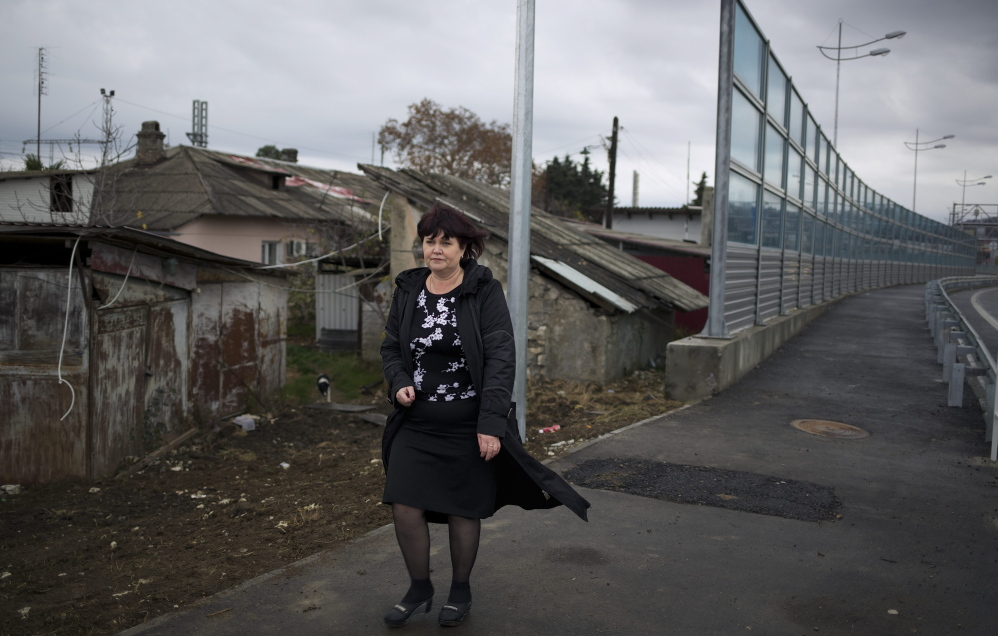 IIrina Kharchenko walks near the screen separating her yard and a federal highway in her village outside Sochi. As the Olympics draw near, many residents complain that their living conditions have become worse and authorities are deaf to their grievances.