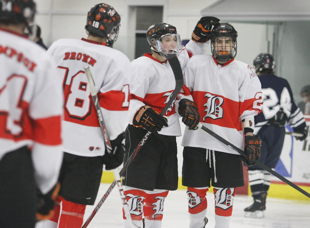 Tyler Bellerose, right, is congratulated by Devon Werthner after scoring a goal Monday during Biddeford's 8-0 hockey win over Portland/Deering.
