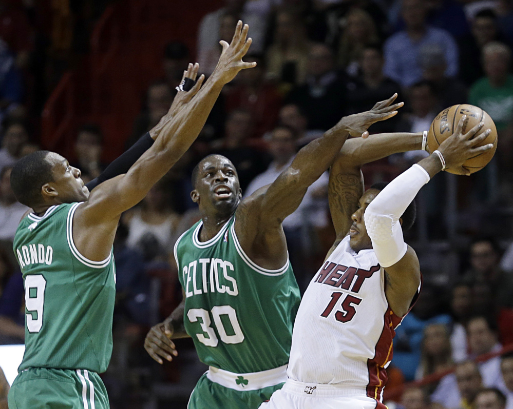 Mario Chalmers of the Miami Heat looks for a teammate Tuesday night while guarded by Rajon Rondo, left, and Brandon Bass of the Boston Celtics in the fourth quarter of Miami's 93-86 victory.