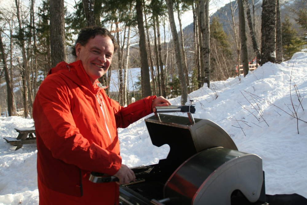 Chef Tony Lawless tends the grill at his winter home at Sunday River in Newry. After suffering from rheumatoid arthritis for decades, he was surprised to find that giving up foods with gluten relieved his pain.