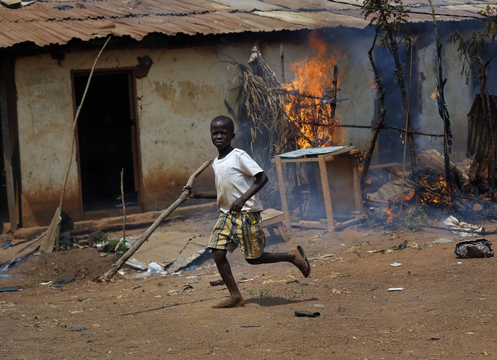 A child runs by a burning house in Bangui, Central African Republic, on Wednesday, where Christan youths looted a Muslim market. Nearly a million people have been displaced by violence since a March 2013 coup.
