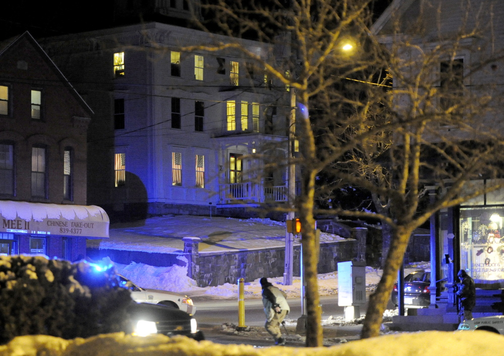 Armed police run in front and stand by on right overlooking the frat house in background during the standoff at USM in Gorham. Wed., January 22, 2014. John Patriquin/Staff Photographer.