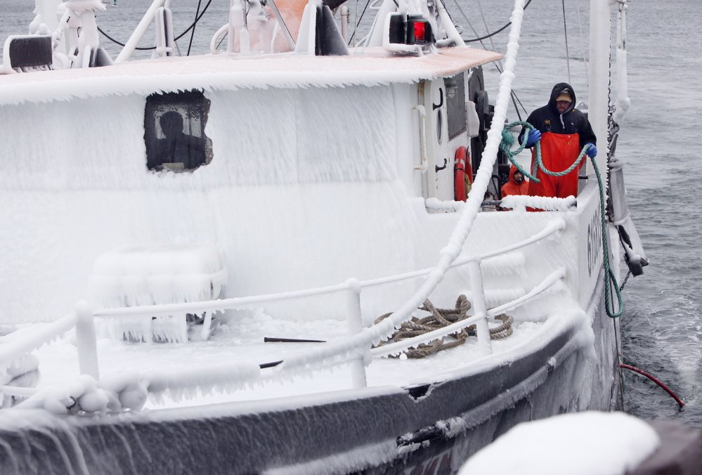 On the side of an iced-over wheelhouse, Larry Rich of Portland prepares to throw a line as the Black Beauty approaches dock on the Portland waterfront on Wednesday morning while returning from an overnight fishing trip.
