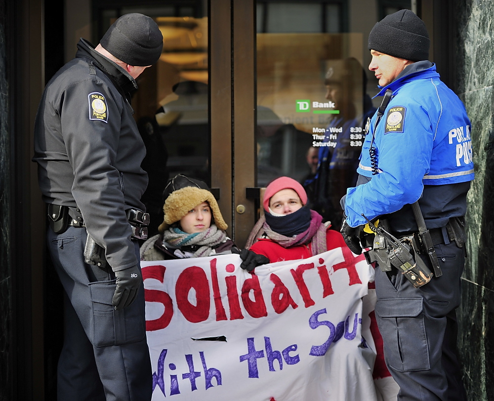 Elizabeth Catlin of Brunswick, seated left, and Seth Schlotterbeck, also known as Sylvia Stormwalker, of Auburn attached themselves with bicycle locks around their necks to the door handles of TD Bank on Congress Street in Portland in a protest against investment in the Keystone XL pipeline. Portland police officers Dave Argitis, left, and Dan Knight stand by them as other officers try to remove the handles from inside the bank on Wednesday.
