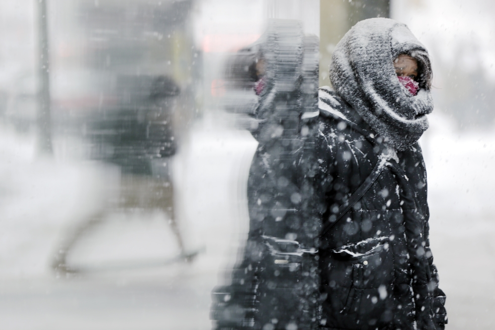 A woman stands at the entrance of a building during a snowstorm Tuesday in Philadelphia.