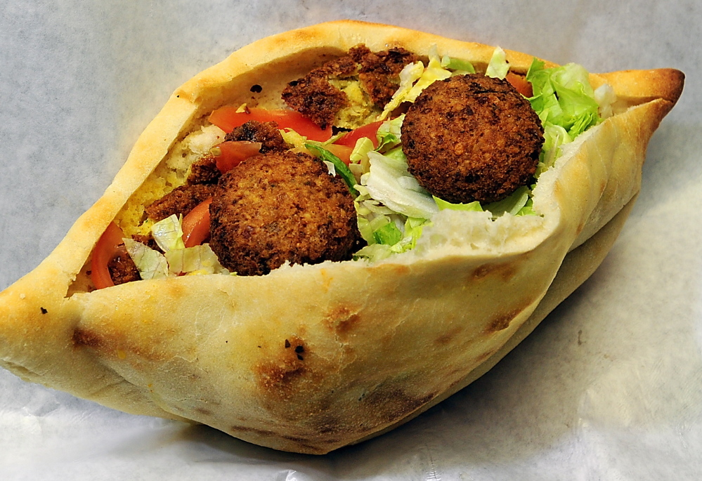 Falafel sandwich with tomato, lettuce, onion and mango sauce on samoon bread.