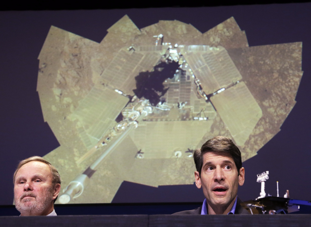 """Mars rovers project manager John Callas, right, and investigator Ray Arvidson attend an event Thursday marking the 10th anniversary of the NASA Mars Opportunity rover mission. Projected at rear is what Callas described as a """"selfie,"""" a self-portrait of the rover's solar panels."""