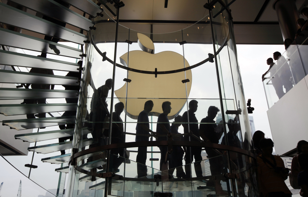 Customers walk past a huge Apple logo at the store in Hong Kong's upscale International Financial Center Mall.