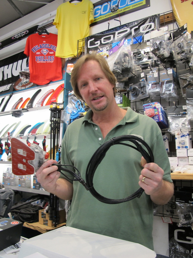 Dennis O'Donnell shows the Shark Shield deterrent device at his Maui store, Hawaiian Island Surf and Sport, in Kahului, Hawaii.