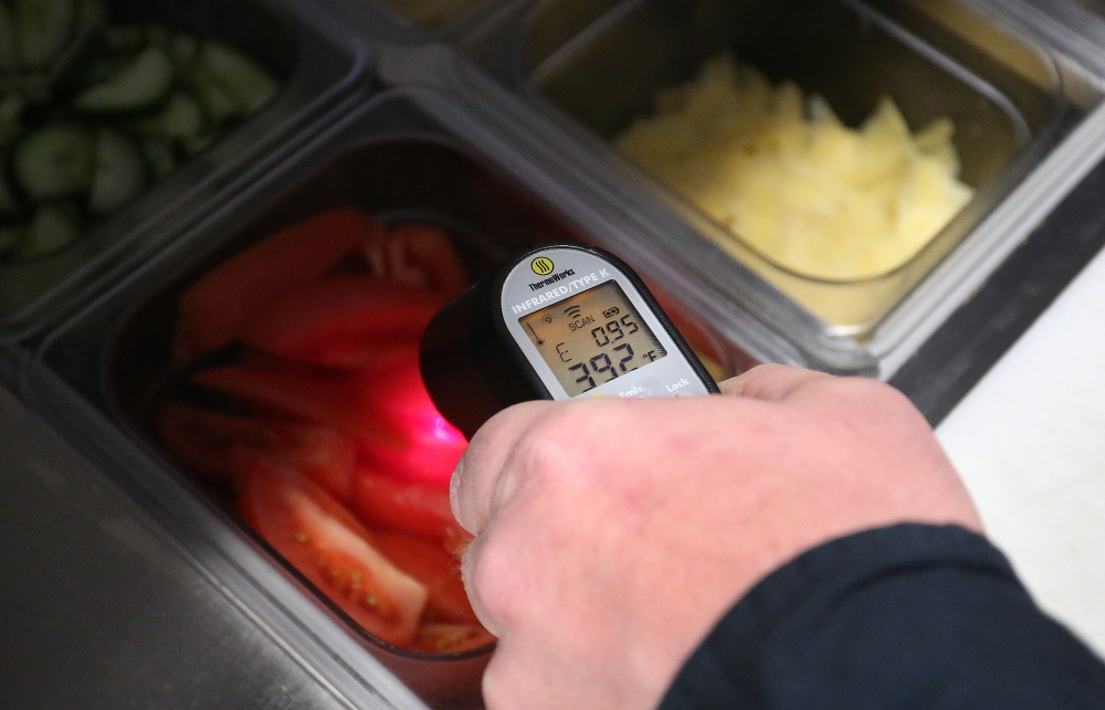 Portland Health Inspector Tom Williams uses a thermometer on Friday to check the temperature of standing vegetables at Buck's Naked BBQ on Wharf Street. A bill would give all Maine communities freedom to inspect restaurants.