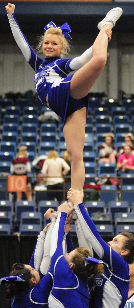 Staff photo by Joe Phelan Flyer Danielle Auge is held aloft by her Lawrence teammates as the Bulldogs compete in the Class A East cheering championship on Saturday January 25, 2014 in the Augusta Civic Center.