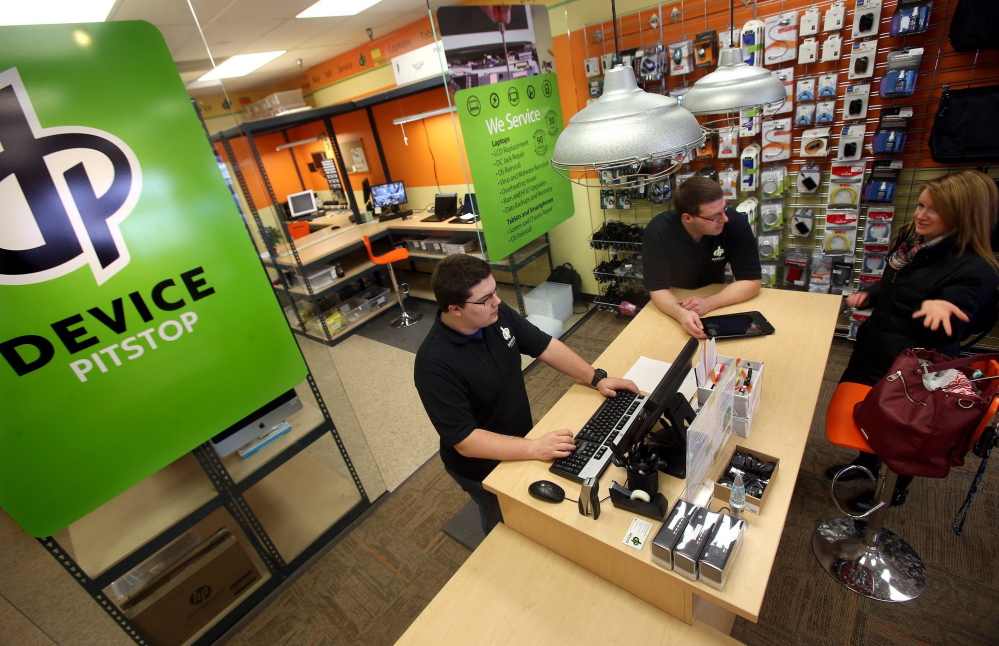 Heath Van Deventer, left, and Dustin Bradford talk with Taylor Hanold about selling her HP Touchpad at Device Pitstop in Minnetonka, Minn., on Jan. 17. The store buys and sells used and refurbished smartphones, laptops, tablets and all-in-one computers.
