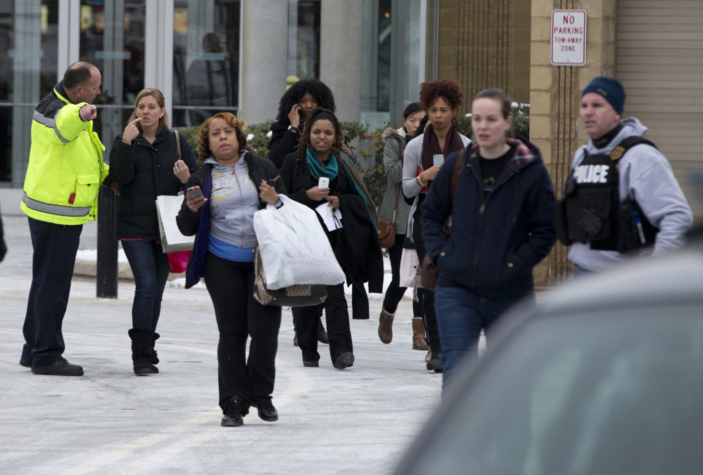 Police and law enforcement evacuate The Mall of Columbia after a shooting on Saturday in Columbia, Md. Police say three people died in a shooting at the mall in suburban Baltimore, including the presumed gunman.