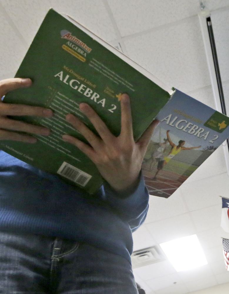 A Texas high school student holds an open algebra II book in math class at Flower Mound High School.