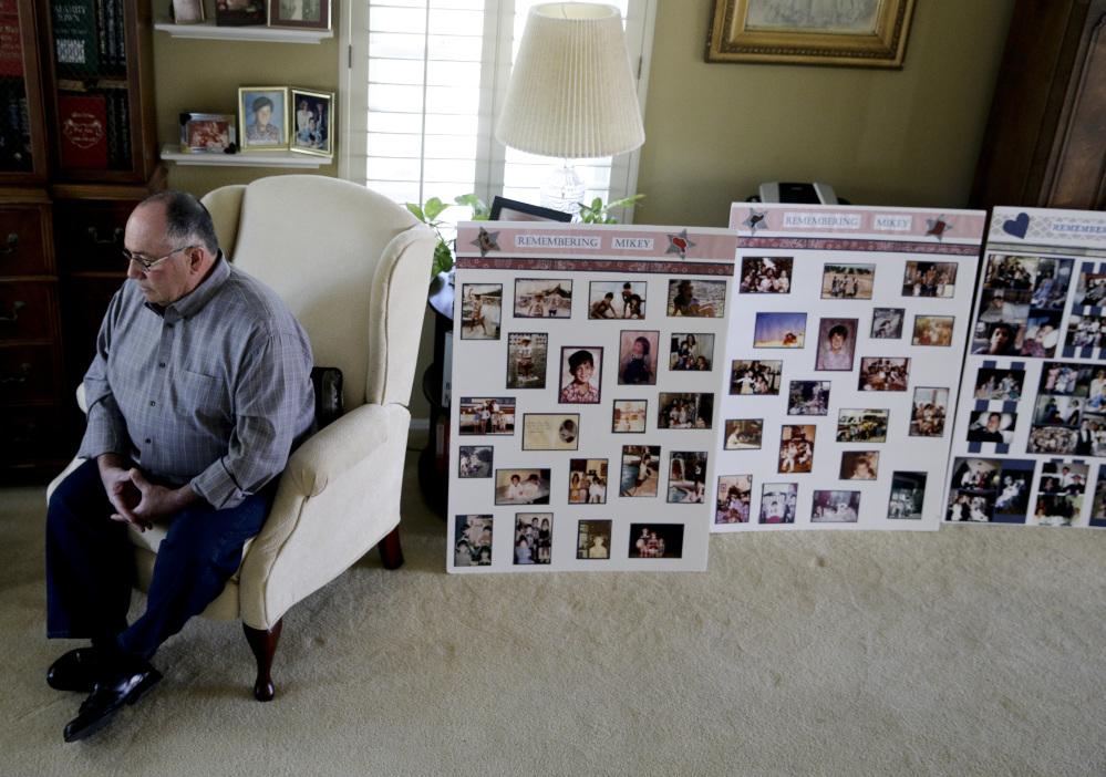 Paul Cortez, father of Mikey Cortez, pauses during an interview while sitting next to memorial boards for his son in Murrieta, Calif.
