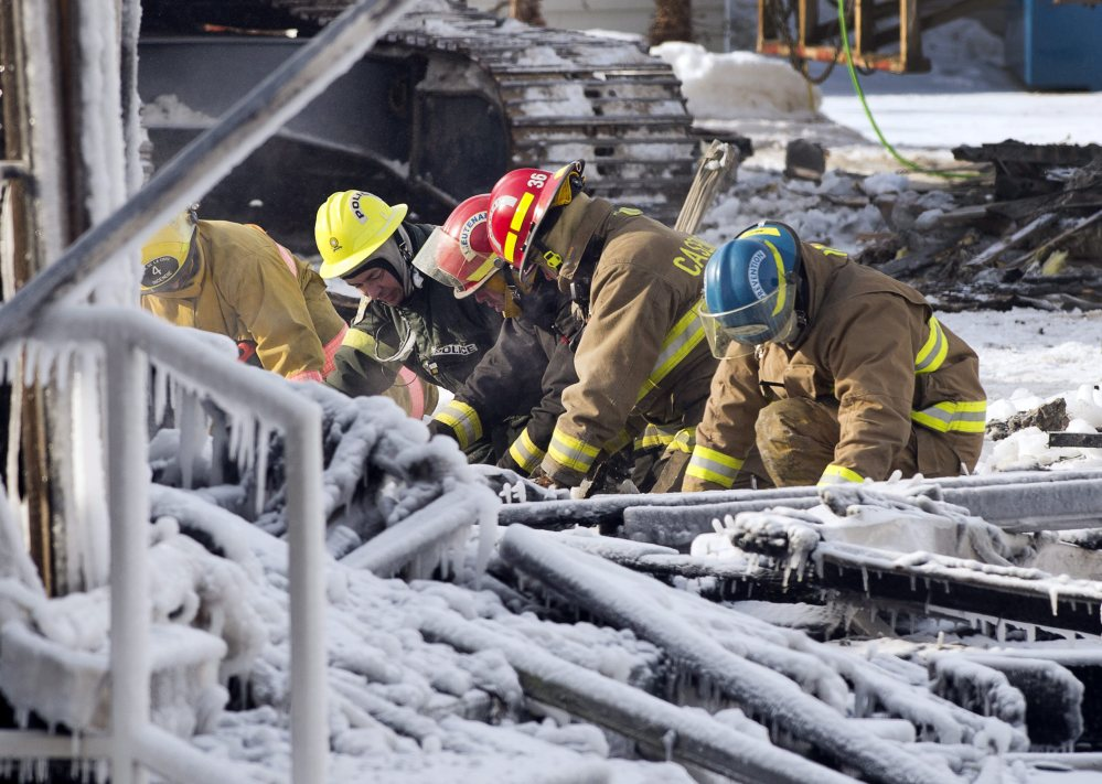 Rescue personnel search through the icy rubble of a fire that destroyed a seniors' residence on Friday in L'Isle-Verte, Quebec. Five people are confirmed dead and 30 people are still missing, while the cause of Thursday morning's blaze is unclear police said.