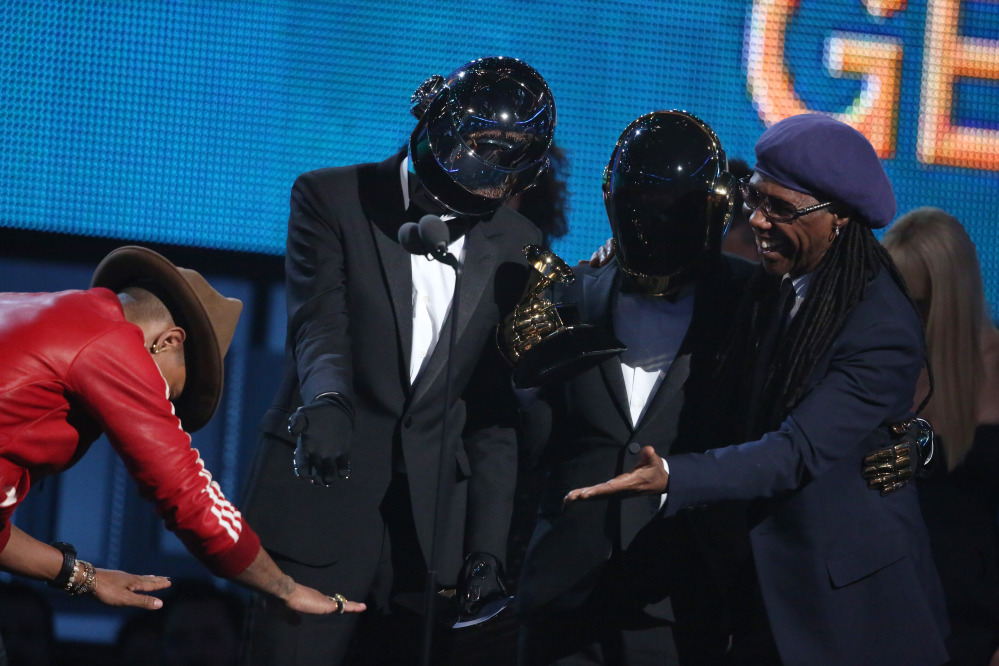 Pharrell Williams, left, presents the award to Thomas Bangalter, second from left, and Guy-Manuel de Homem-Christo of Daft Punk, and Nile Rodgers for Best Pop Duo/Group Performance for