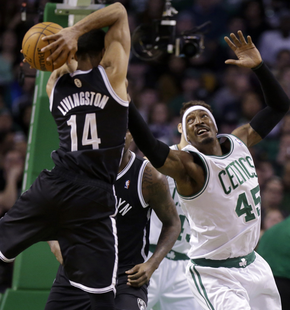 Brooklyn's Shaun Livingston vies for control of the ball against tenacious Boston Celtics forward Gerald Wallace during first-quarter action Sunday in Boston.