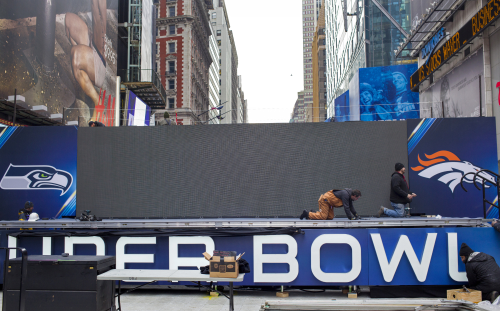 A stage structure with the logos of the Seattle Seahawks and the Denver Broncos comes together Monday in New York's Times Square. Up to 13 blocks in the heart of Manhattan will close to traffic for four days so the NFL can host a Super Bowl festival called Super Bowl Boulevard.