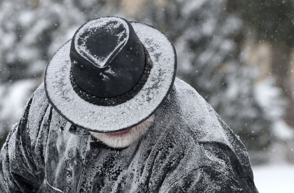 Roger Homrich has snow accumulate on his hat and jacket as he clears snow from a Bridge St. sidewalk in Grand Rapids, Mich., Monday, Jan. 27, 2014. Grand Rapids is experiencing single digit temperatures and sub-zero wind chills.