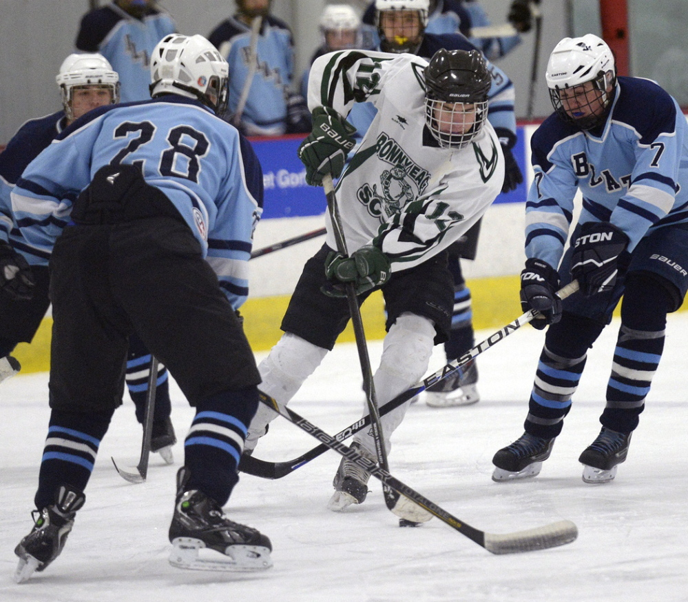 Bonny Eagle's Justin Miles tries to maneuver between Westbrook's David Redmond, left, and Elijah Doucette in Monday's boys' hockey game at Gorham. The Scots won 3-2, scoring all their goals in the first period.