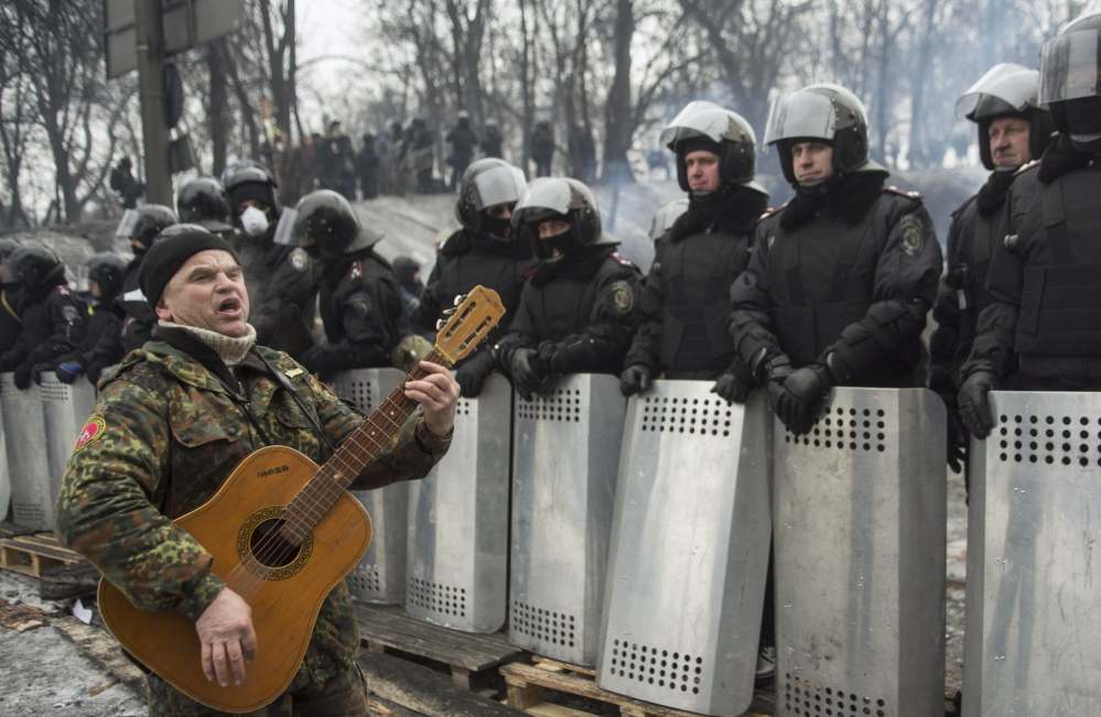 An anti-government activist plays the guitar Tuesday in front of riot police at the site of clashes in Kiev.