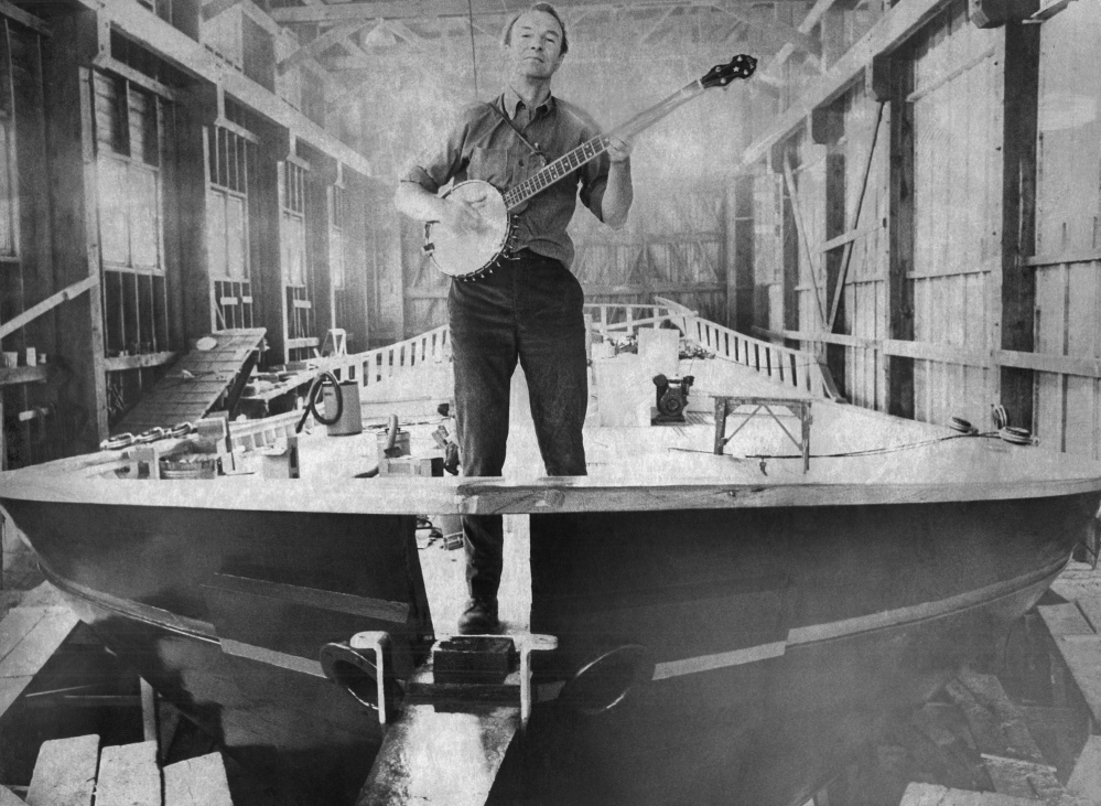 Folk singer Pete Seeger strums a banjo on the bow of his 75-foot sloop to be launched in South Bristol, Maine on May 14, 1969. Seeger and a group of volunteers had $150,000 vessel built to dramatize the fight against pollution of Hudson River Valley. (AP Photo/Stephen Nichols)