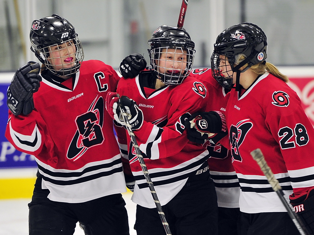 Elizabeth Gross, center, who scored three goals, celebrates with Brenna Kent, left, and Alyssa Hulst as Scarborough moved within one game of a perfect regular season with a 5-1 victory Tuesday against Leavitt/Edward Little at Auburn.