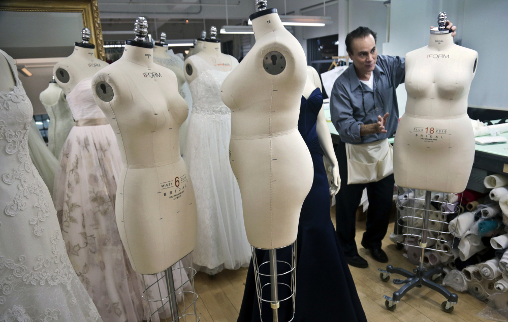 Noel Belancourt, a dressmaker at David's Bridal, wheels a plus-size mannequin to his workstation in New York. David's, the nation's largest bridal chain, is changing its mannequins to create gowns to reflect the average body.