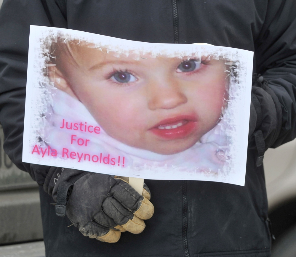 A poster with the image of missing child Ayla Reynolds is held by a demonstrator at the police department Saturday in Waterville, where protesters called for charges to be filed against the people who were with Ayla when she disappeared more than two years ago.