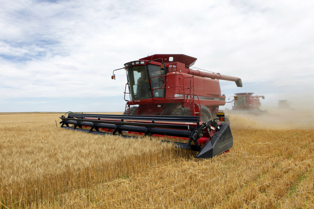 Three combines harvest winter wheat near Roggen, Colo. The House passed a farm bill Wednesday that continues to heavily subsidize major crops.
