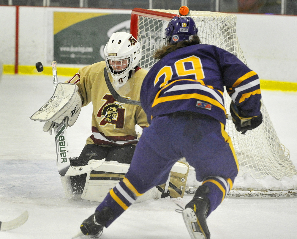 Thornton Academy goalie Andrew Huot bats aside a shot on goal by Conor Ryle of Cheverus during the first period of Thornton's 4-3 overtime victory Wednesday night at the Biddeford Ice Arena. Thornton won after scoring two late goals to force overtime.